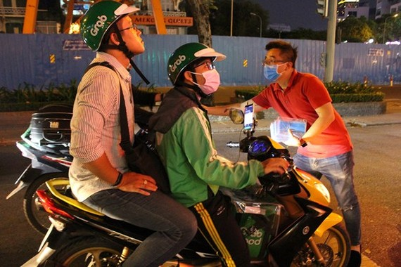 A young man gives free facemasks to people in Nam Ky Khoi Nghia Street in HCMC (Photo: SGGP)