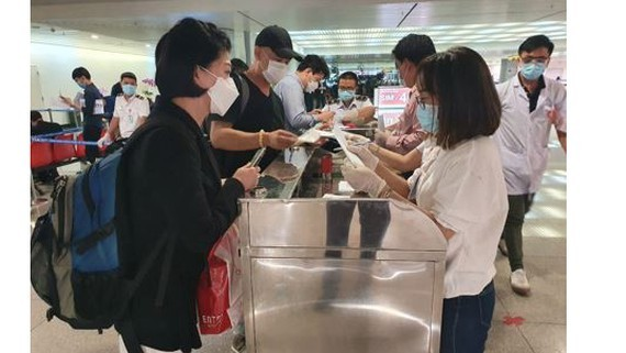 People from South Korea are filling health declararion forms at Tan Son Nhat airport(Photo: SGGP)