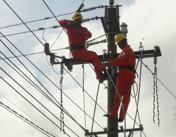 Wokers of the Electricity of Vietnam in Quang Binh Province checking the power grid. The Ministry of Industry and Trade was raising new retail electricity tariff options for comments. - VNA/VNS Photo