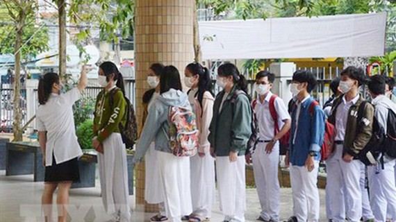 Students of Phan Chau Trinh High School in Da Nang City are standing in line to have their temperature checked. (Photo: VNA)