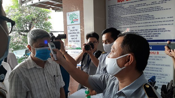 A medical worker measures temperature ofDeputy Health Minister Nguyen Truong Son (Photo: SGGP)