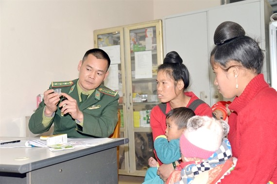 A military doctor from Phieng Pan border station in Sơn La Province instructs the local people on how to use medicine. — VNA/VNS Photo