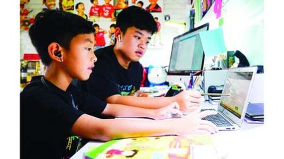 Third-grader Nguyen Huynh Thong is getting used to e-learning with the help of his brother, a seventh grader. (Photo: SGGP)