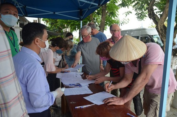 Foreigners are writing information at one of checkpoints in Da Nang (Photo: SGGP)