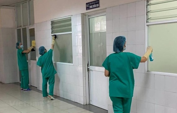 Medical workers clean COVID-19 patient rooms (Photo: VNA)