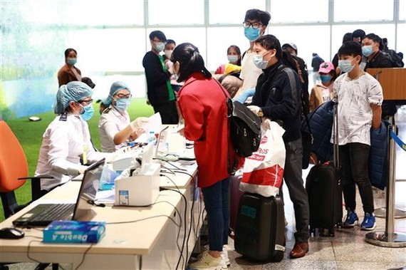 Passengers line up to wait to complete compulsory health declaration procedures at Noi Bai airport. — VNA/VNS Photo