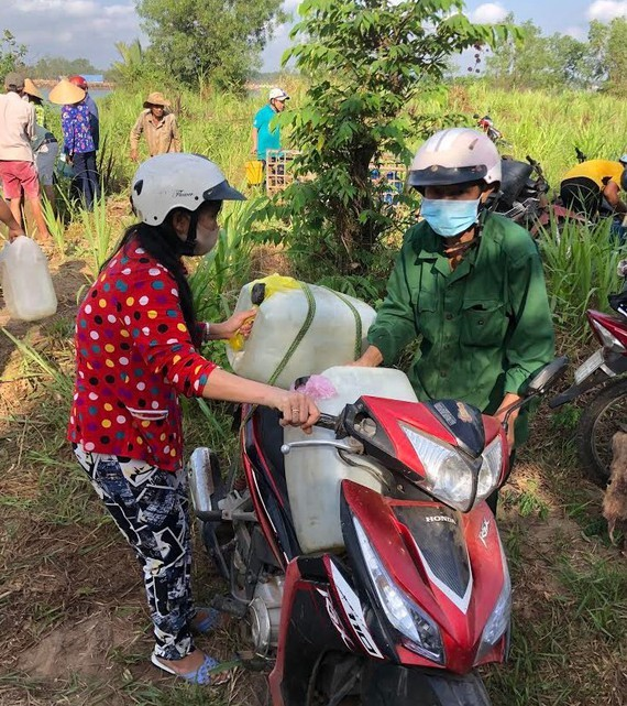 Residents carry plastic containers to take water home (Photo:SGGP)
