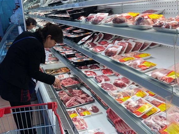 A woman shops for pork in a supermarket in Hano. — VNA/VNS Photo