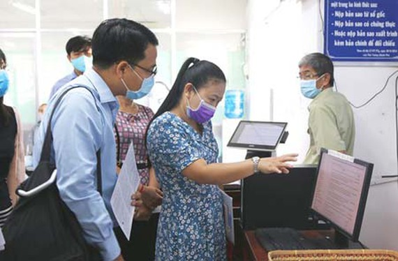 Citizens are learning about online public services at the People's Committee of Hoc Mon District. (Photo: SGGP)