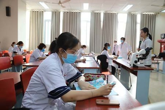 Students of HCMC University of Medicine and Pharmacy strictly observe protection rules when coming to school. (Photo: SGGP)