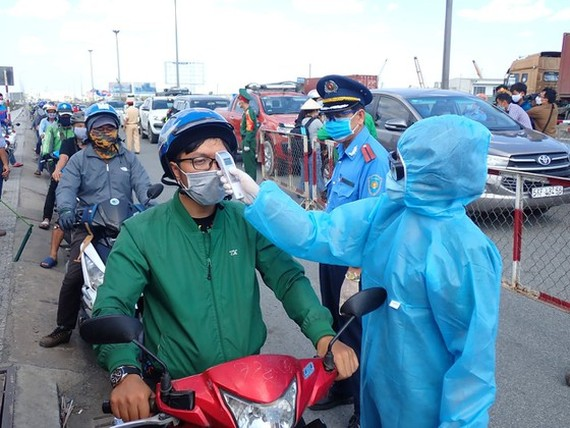 A driver has his body temperature taken before entering Ho Chi Minh City (Photo: SGGP)