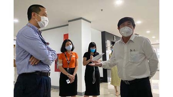 Chairman of HCMC People's Committee Nguyen Thanh Phong is inspecting the safety status against Covid-19 in FPT Software Co. Ltd. (Photo: SGGP)