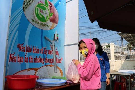 Poor people receive rice from the rice ATM in Ca Mau (Photo: SGGP)