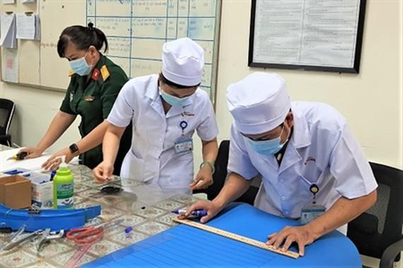 Medical workers make anti-bacterial face masks, protective plastic visors