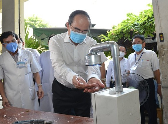 Secretary of the Ho Chi Minh City Party Committee Nguyen Thien Nhan washes his hand at automatic hand sanitizer dispenser at Thong Nhat Hospital (Photo: SGGP)