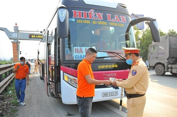 A traffic officer checks a driver's paperwork on National Highway 1A. (Photo: VNA)