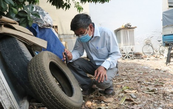 A medical worker is checking tyre dump site, a dengue hazard (Photo: SGGP)