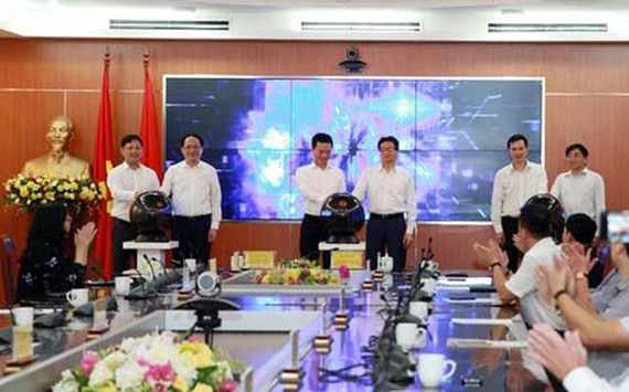 Deputy PM Vu Duc Dam, Minister of Information and Communications Nguyen Manh Hung, and other delegates press the button to officially launch Vpostcode platform. (Photo: VNP)