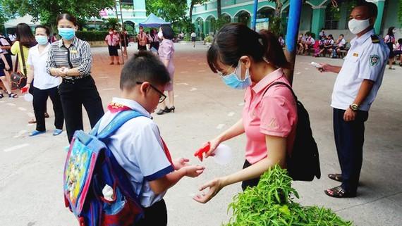 A teacher sprays hand sanitizer on a little child of An Hoi School in Go Vap District (Photo: SGGP)