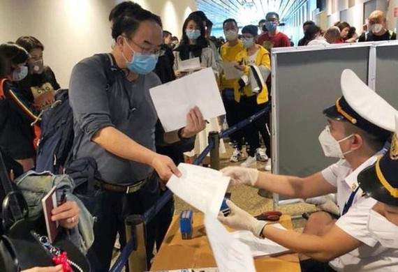 People from oversea write mandatory health declarations at Tan Son Nhat Airport (Photo: SGGP)