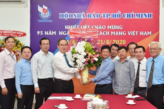 Mr. Nhan gives a bunch of flower to leaders and reporters of the city's Press Association (Photo: SGGP)