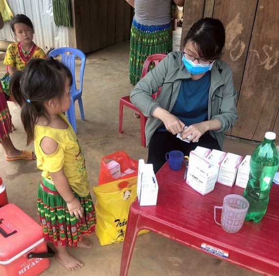 A medial worker is examining a etnic minority child in Dak Nong (Photo: SGGP)
