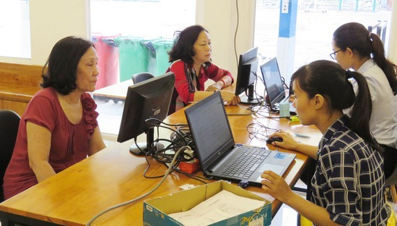 Staffs and teachers at primary and junior high schools in Tan Binh District are present to help parents without laptops at homes to register online at schools (Photo: SGGP)