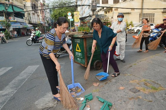 People clean streets in response to city authorities' campaign (Photo: SGGP)