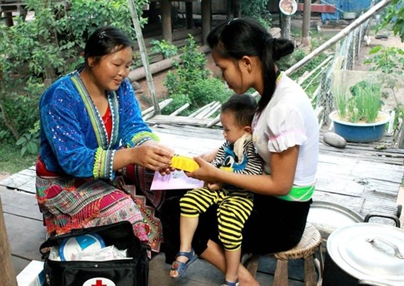A village-based midwife gives health care guidance to a mother in Muong Nhe district, the northern mountainous province of Dien Bien. (Photo: VNA)