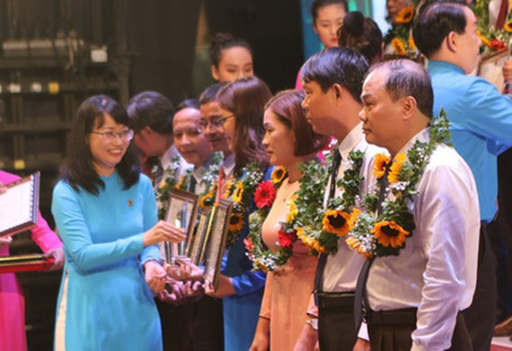 Head of HCMC Federation of Labor Tran Thi Dieu Thuy delivered awards to outstanding laborers in HCMC. (Photo: SGGP)