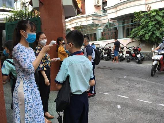 Teachers of Kien Thiet High School in District 3 take students' temperature (Photo: Dan Thuy)