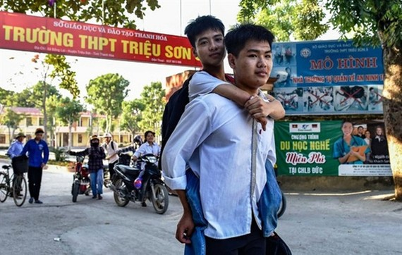 Ngo Minh Hieu carries his classmate Nguyen Tat Minh on his back to school every day. — Photo: nld.com.vn