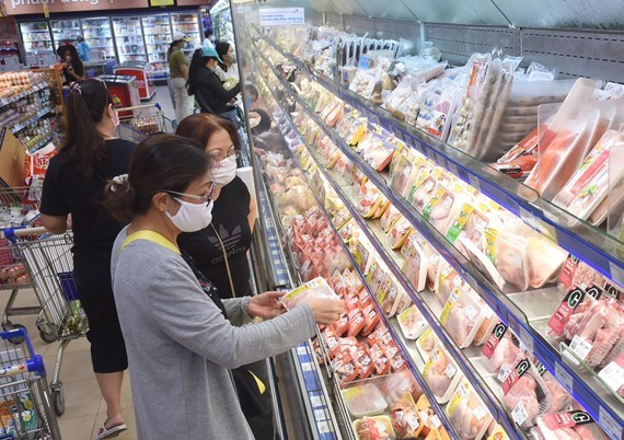 Consumers are choosing pork at a supermarket in HCMC (Photo: SGGP)