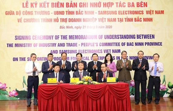 Delegates from Ministry of Industry and Trade, People's Committee of Bac Ninh province, and Samsung Electronics Vietnam sign the memorandum of understanding (Source: VNA)
