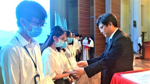 Deputy Director of the National University of Ho Chi Minh City Nguyen Minh Tam awards scholarships to students with financial difficulties and good performance (Photo: SGGP)