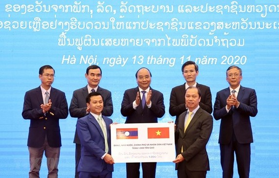 Deputy Minister of Foreign Affairs Nguyen Quoc Dung (R) hands over the token of the relief aid of 1,000 tonnes of rice from the Vietnamese Government to Lao Deputy Ambassador to Vietnam Chanthaphone Khammanichanh (Photo: VNA)