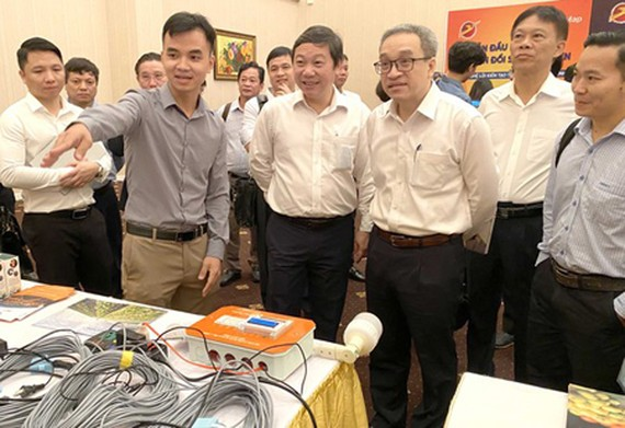 Deputy Minister of Information and Communications Phan Tam, Vice Chairman of HCMC People's Committee Duong Anh Duc, and other delegates are visiting the ICT product exhibition