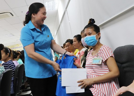 A representative of a trade union gives gift to pregnant workers (Photo:SGGP)