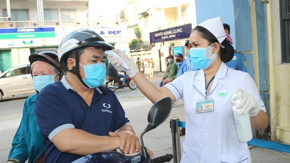Relatives of patients are measured temperature before entering a hospital in HCMC (Photo: SGGP)