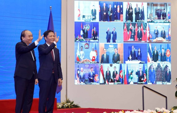 Vietnamese Prime Minister Nguyen Xuan Phuc (left) and Minister of Industry and Trade Tran Tuan Anh, together with leaders of other RCEP member countries, witness the pact signing via videoconference on November 15 (Photo: VNA)