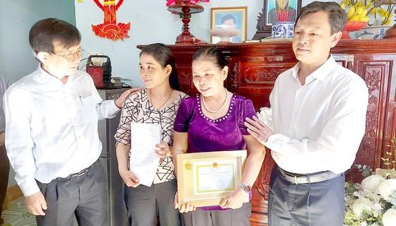 Pham Thi Mai ( purple) receives the medal (Photo: SGGP)