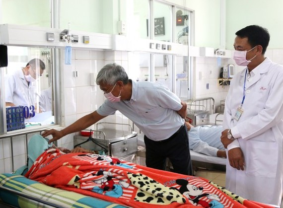 Deputy chairman of HCMC People's Committee Vo Van Hoan (L) visits patients at a hospital in Binh Phuoc Province (Photo: SGGP)