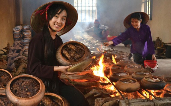 Villagers are cooking the famous braised fish (Photo: SGGP)
