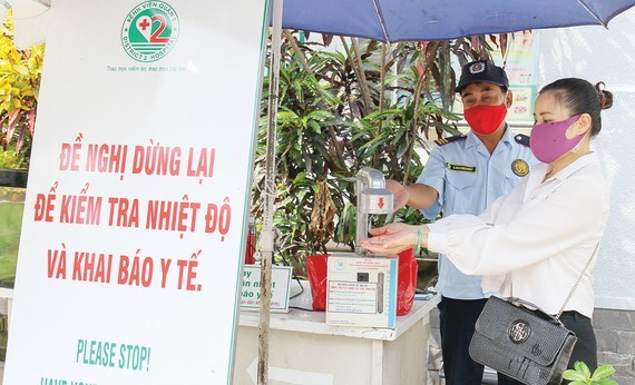 People are instructed to wash their hands with disinfectant before entering patients' rooms (Photo: SGGP)