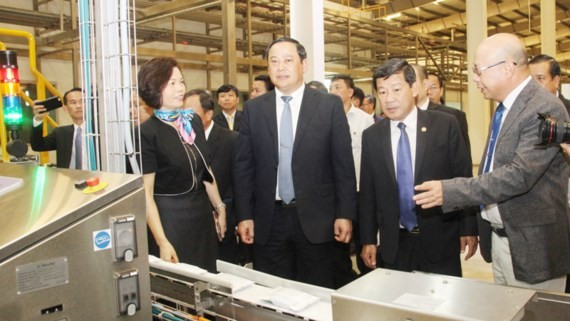 Lao Deputy Prime Minister Sonexay Siphandone visits a factory of Vietnam Dairy Products Joint - Stock Company