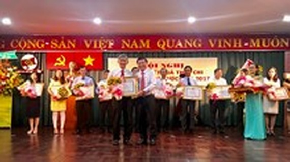 Chairman of the HCMC People's Committee Nguyen Thanh Phong certificates for enterprises with their great achievements in State budget remittance this year.