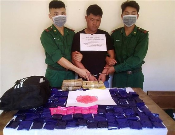 The arrested Lao national and seized exhibits (Photo: VNA)