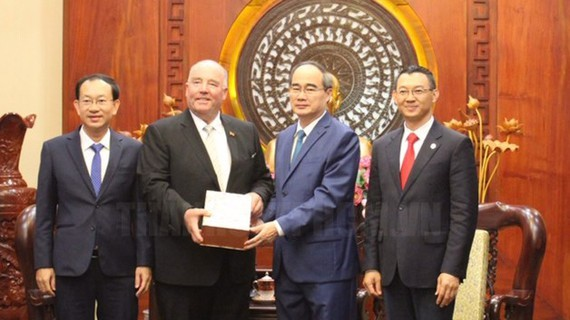 Secretary of the Party Committee of Ho Chi Minh City Nguyen Thien Nhan offers a souvenir to  former Ambassador of Germany to Vietnam Rolf Schulze