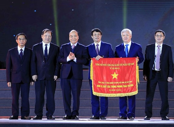 Prime Minister Nguyen Xuan Phuc (third from left) presents the Government's Emulation Flag to the Vietnam National Cement Corporation.