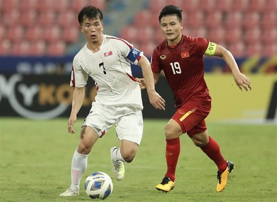 Team captains of Vietnam Nguyen Quang Hai (in red) and the DPRK Ri Chung-gyu vie for the ball (Photo: VNA)